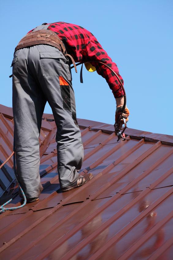 Contractor Repairing Metal Roofing